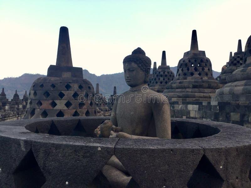 Figura de Buddha que se sienta Templo budista de Borobudur Cerca de Yogyakarta en Java Island, Indonesia foto de archivo libre de regalías
