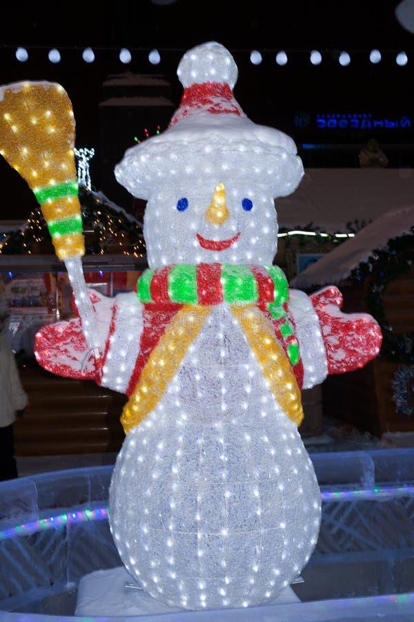 A figura de incandescência de um boneco de neve de sorriso em um fundo preto imagens de stock royalty free