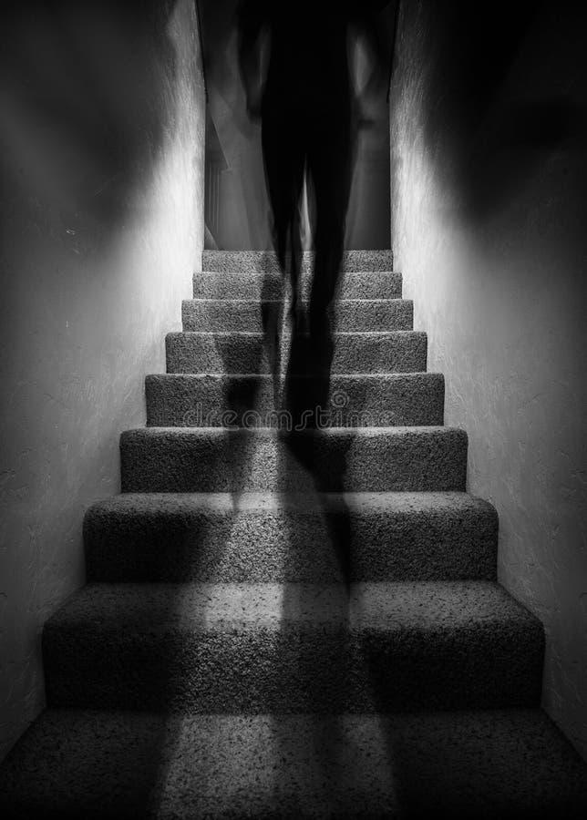 Figura de la sombra que camina encima de las escaleras imagen de archivo