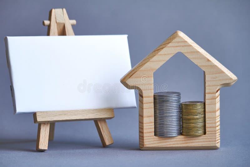 Figura de madeira da casa com as duas colunas das moedas internas e placa branca na armação diminuta no fundo cinzento, o conceit foto de stock