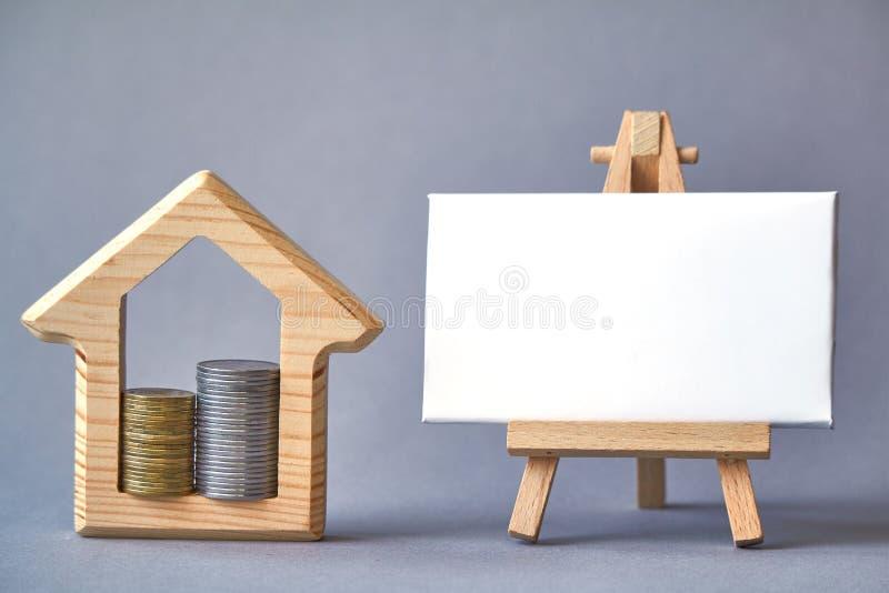 Figura de madeira da casa com as duas colunas das moedas internas e placa branca na armação diminuta no fundo cinzento, o conceit fotografia de stock