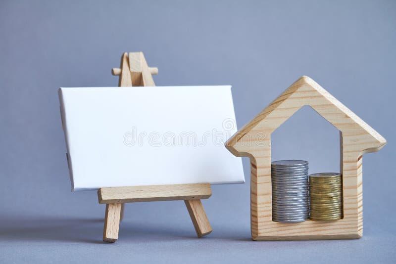 Figura de madeira da casa com as duas colunas das moedas internas e placa branca na armação diminuta no fundo cinzento, o conceit imagem de stock