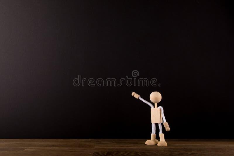 Figura de madeira da vara que aponta no quadro-negro do quadro Conceptual Lugar para seu texto foto de stock