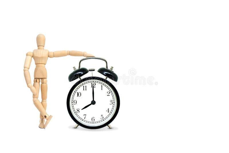 A figura de madeira manequim pôs a mão sobre o despertador preto retro que exibição oito horas imagens de stock royalty free