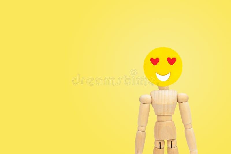 A figura de madeira tem o sentimento no amor da emoção da cara com fundo amarelo fotos de stock royalty free