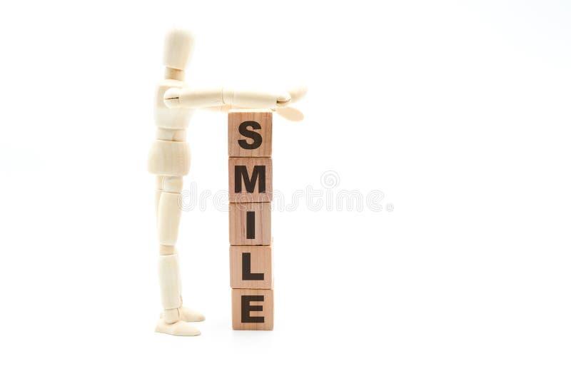 Figura de madera como sonrisa del edificio del hombre de negocios como torre de los cubos de madera fotografía de archivo