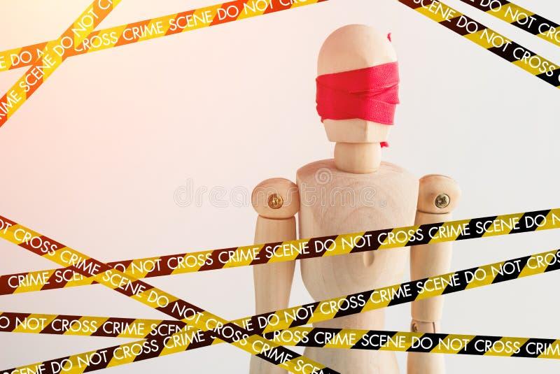 Figura de madera persiana del hombre con la cinta roja con la línea de policía sce del crimen foto de archivo libre de regalías