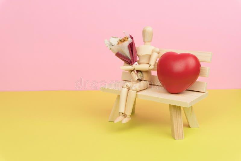 Figura de madera que sostiene un ramo de flor secada y que se sienta en el banco de madera con un corazón rojo del amor fotografía de archivo