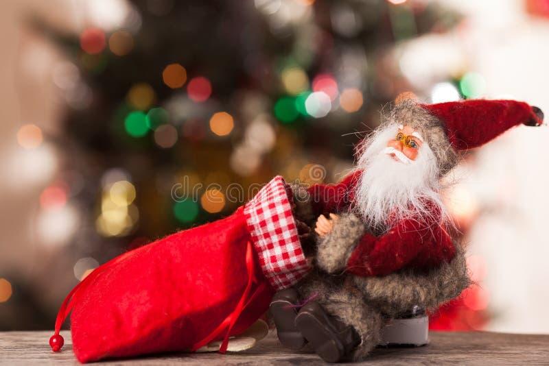 Figura de Papá Noel con un bolso de regalos en el boke imagen de archivo