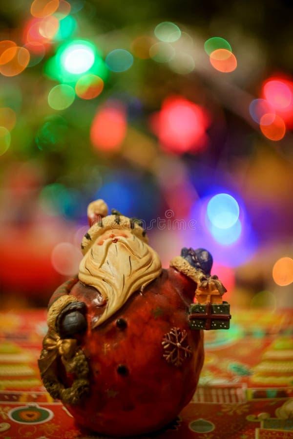 Figura de Santa Cláusula en un fondo multicolor de las luces de boquilla fotos de archivo