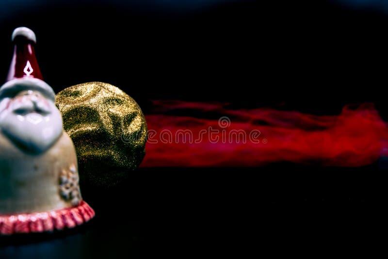 Figura de Santa Claus, bola brillada de oro de la Navidad y fabr rojo foto de archivo