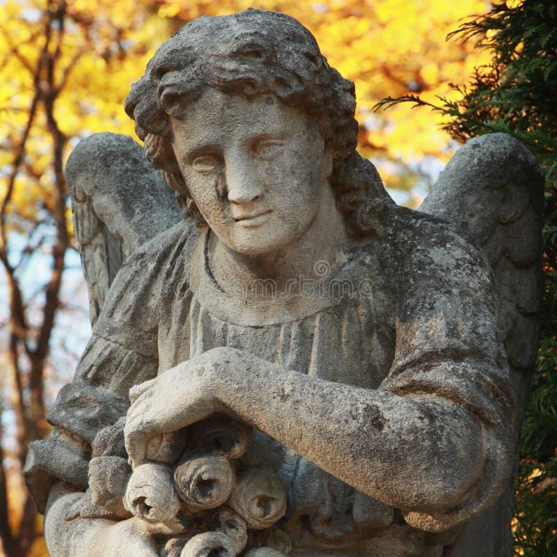 A figura de um anjo rezando no ouro sae fotografia de stock