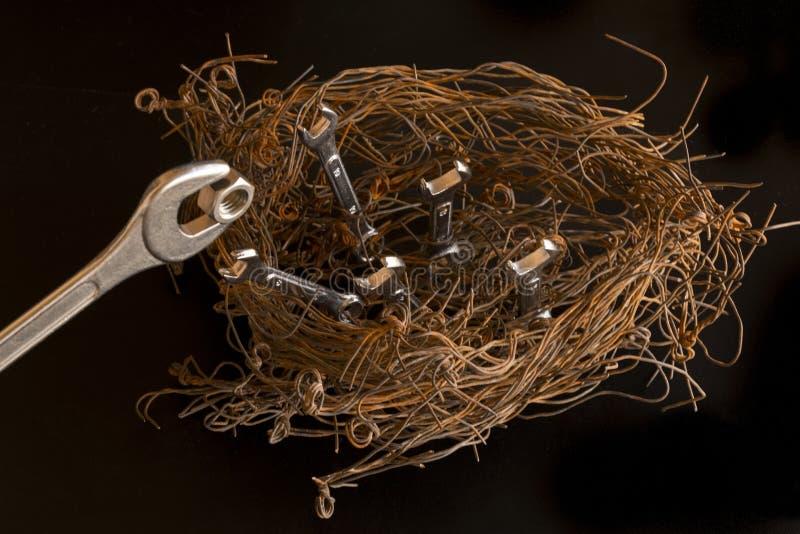 Figura de um ninho dos pássaros feito com fios de aço e chaves O maior deles simula ser a mãe que alimenta uma porca ao fotografia de stock