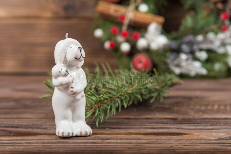 A figura de um urso polar com um bebê em seus braços Brinquedos do Natal Grinalda Quadro do inverno do Natal no fundo de madeira  imagens de stock