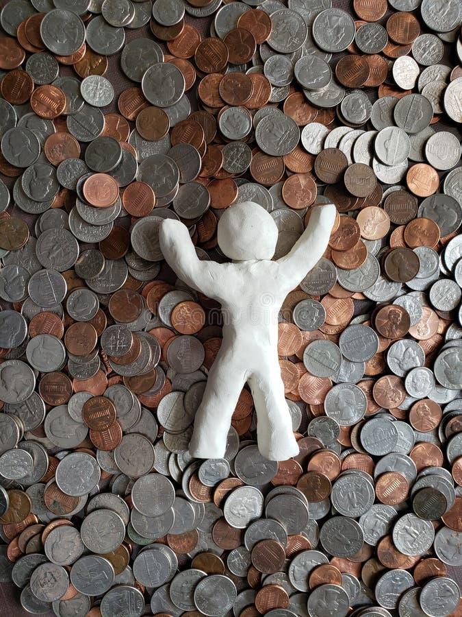 figura de uma pessoa que descansa no dinheiro, feita com argila e fundo brancos com moedas de um centavo do dólar fotografia de stock royalty free