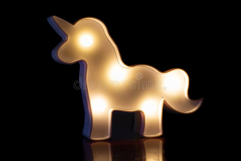 Figura de un caballo que brilla intensamente blanco en un fondo negro con una reflexión hermosa fotografía de archivo libre de regalías