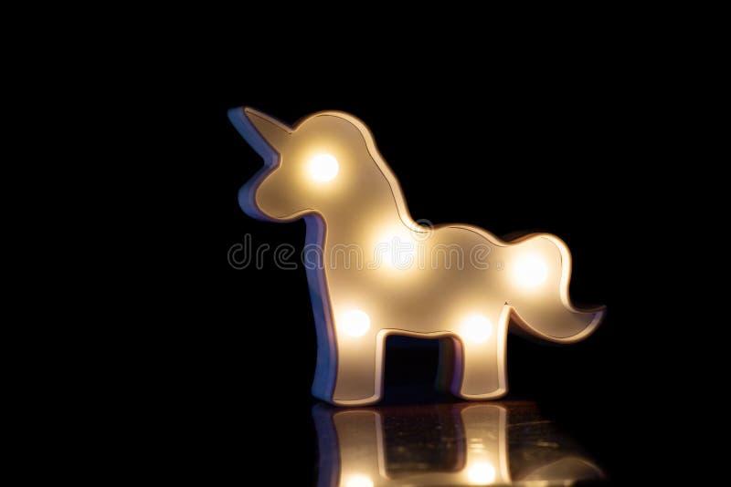 Figura de un caballo que brilla intensamente blanco en un fondo negro con una reflexión hermosa foto de archivo