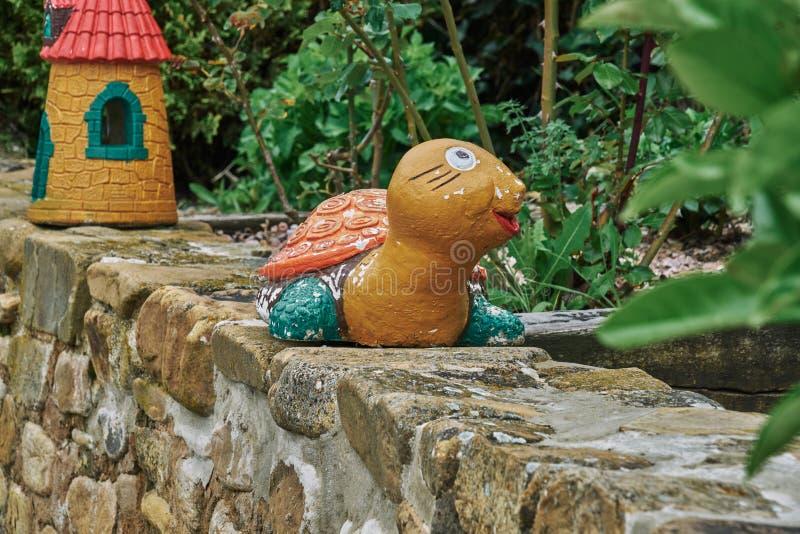 Figura decorativa del jardín en la forma de una tortuga y al lado de molinos fotos de archivo