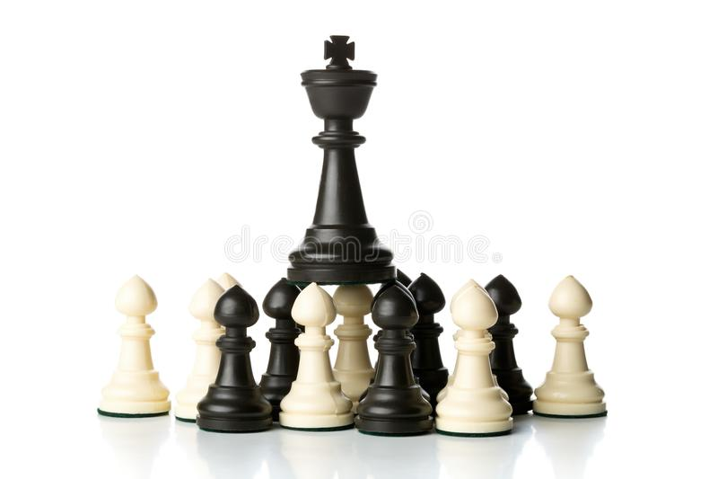 Figura del ajedrez del rey encima de figuras del ajedrez del empeño foto de archivo