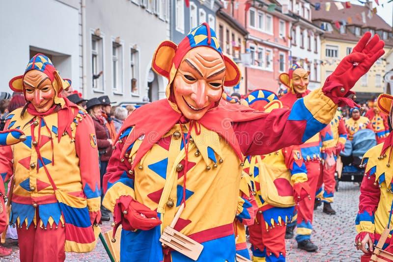 Figura del carnaval con los oídos grandes y la cara larga en traje amarillo, rojo Carnaval de la calle en Alemania meridional - b fotografía de archivo