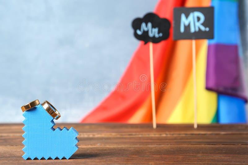 Figura del cuore con le fedi nuziali e la bandiera dell'arcobaleno fotografie stock libere da diritti