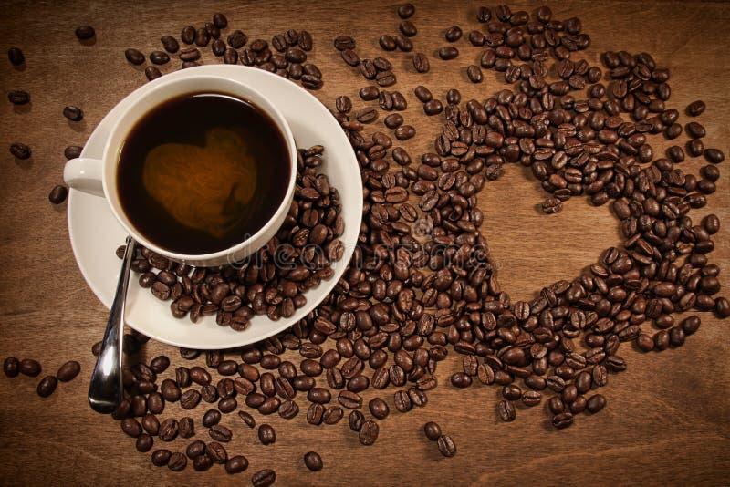 Figura del cuore dai chicchi di caffè su legno fotografia stock libera da diritti
