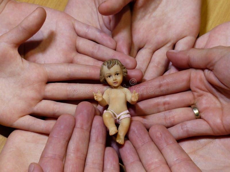 Figura del liyng di Gesù del bambino sulle mani di una famiglia e di una fede nuziale fotografia stock libera da diritti