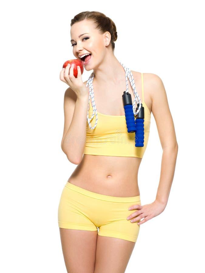 Figura delgada de la mujer que come una manzana fresca roja fotos de archivo