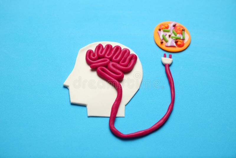 Figura dell'uomo con il cervello e la pizza di alto-caloria Alimento per la mente fotografia stock libera da diritti