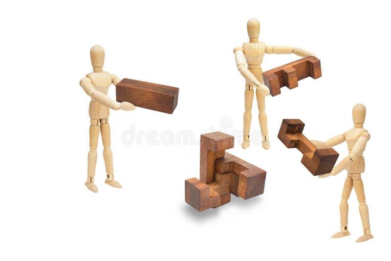 Figura di legno manichino che tiene e che risolve puzzle di legno isolato su fondo bianco illustrazione di stock