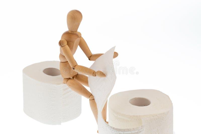 Figura di legno su una carta igienica del rullo fotografia stock