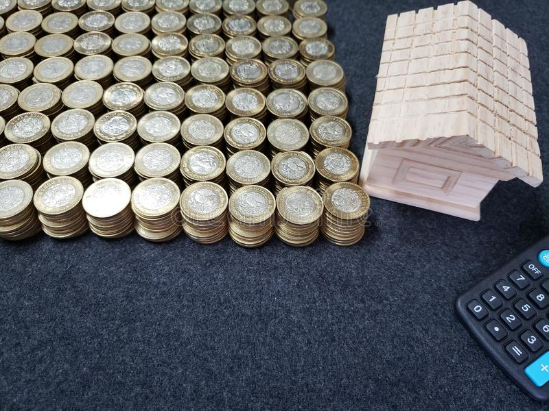 figura di legno di una casa, di un calcolatore e delle monete di dieci pesi messicani immagini stock libere da diritti