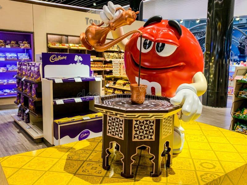 Figura di M&M che versa caffè turco in una tazza Adattamento della pubblicità della caramella della società MARTE per le regioni  immagine stock libera da diritti