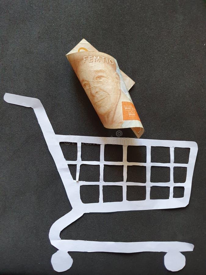figura di un carrello su Libro Bianco e su soldi svedesi immagini stock