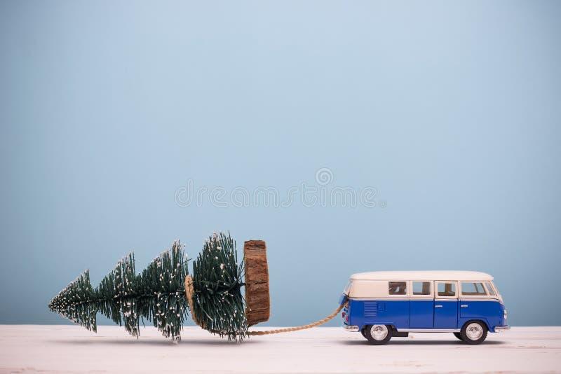 Figura diminuta árvore de Natal do arrasto do carro do brinquedo em de madeira fotos de stock royalty free