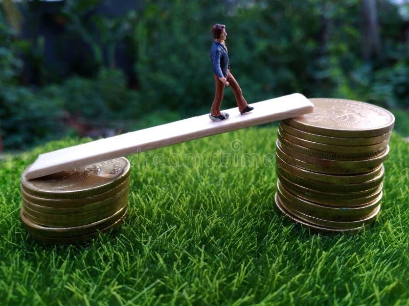 A figura diminuta bussinesman novo mantém-se tentar obter uma renda mais alta que anda na pilha de moeda na grama verde fresca na fotos de stock royalty free
