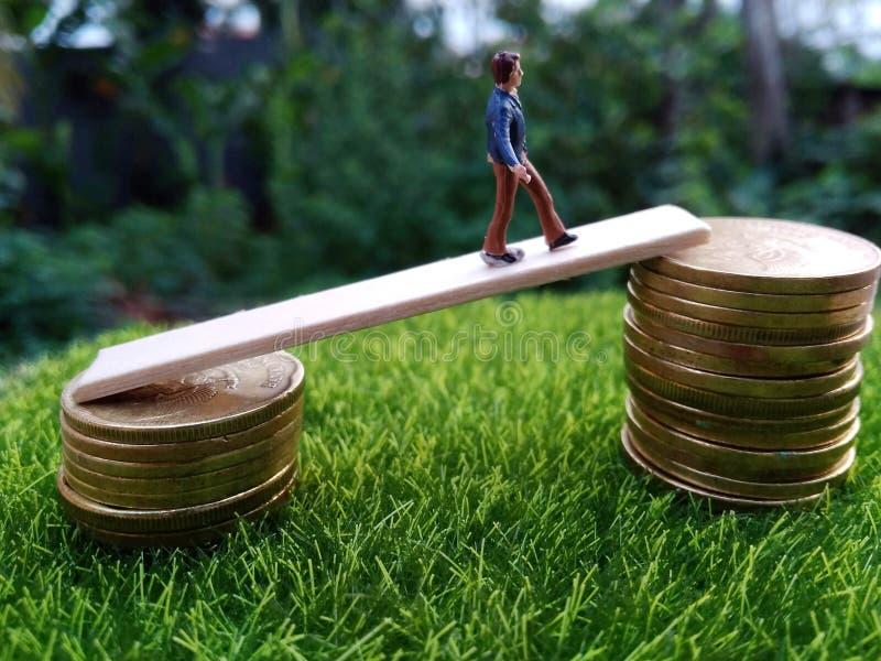 A figura diminuta bussinesman novo mantém-se tentar obter uma renda mais alta que anda na pilha de moeda na grama verde fresca na fotos de stock