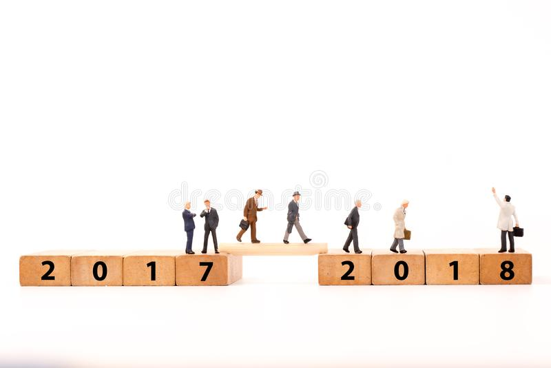 Figura diminuta homem de negócios que anda no bloco de madeira do número transversalmente desde 2017 até 2018 fotos de stock
