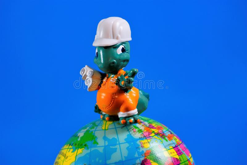 Figura do brinquedo das crian?as - arquiteto-construtor com os desenhos no globo da terra O brinquedo ? um modelo reduzido de um  fotos de stock royalty free