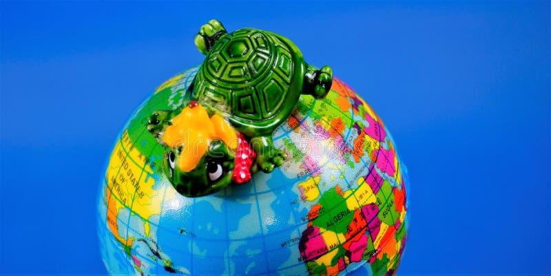Figura do brinquedo das crianças - tartaruga no globo da terra O brinquedo ? um modelo reduzido de uma criatura imagin?ria De aco imagem de stock royalty free