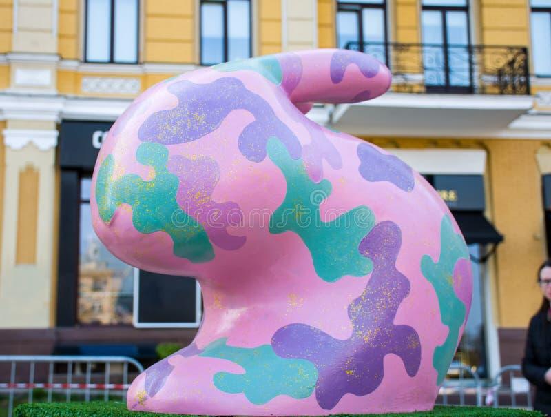 Figura do coelhinho da Páscoa cor-de-rosa com camuflagem das forças armadas pontos verdes, violetas e roxos colorindo próximos no fotos de stock