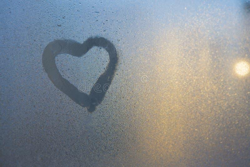 Figura do coração em uma janela congelada na cidade imagem de stock