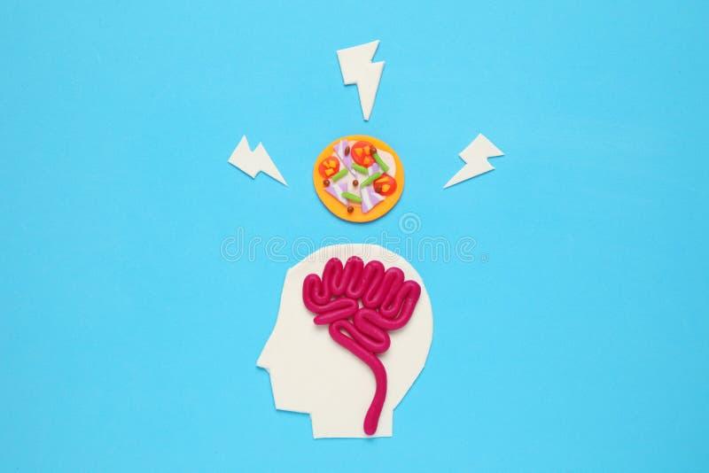 Figura do homem com cérebro e pizza de alto-caloria Alimento para a mente fotografia de stock royalty free