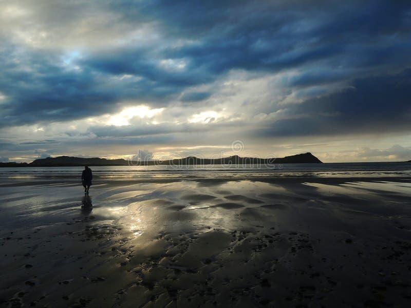 Figura do homem na praia da Irlanda após a chuva fotografia de stock royalty free