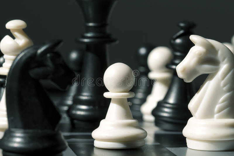 Figura empeño del ajedrez en el tablero Empeño blanco en figuras negras en el tablero de ajedrez foto de archivo
