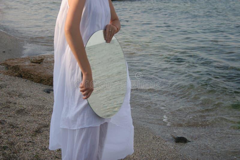 Figura fêmea com um espelho no litoral imagens de stock royalty free