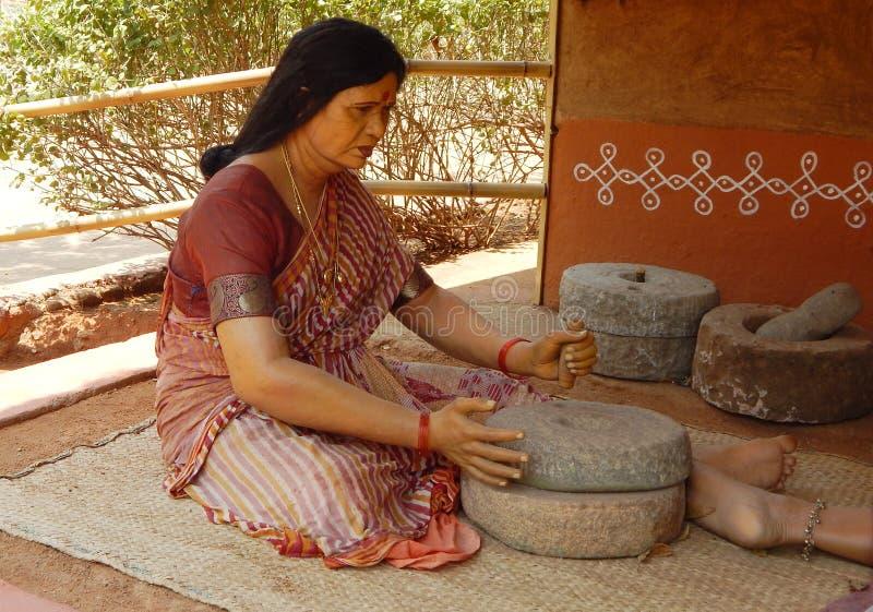Figura india rural de la mujer usando la amoladora de piedra para hacer la harina foto de archivo libre de regalías