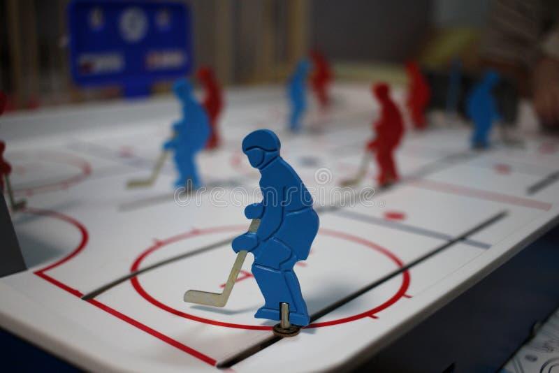 Figura jugador de hockey del hombre del juguete con el palillo del pl?stico en hockey de la tabla fotografía de archivo libre de regalías