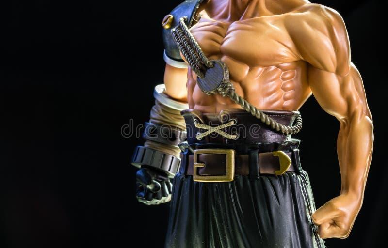 Figura juguete del guerrero del hombre fuerte en fondo negro foto de archivo