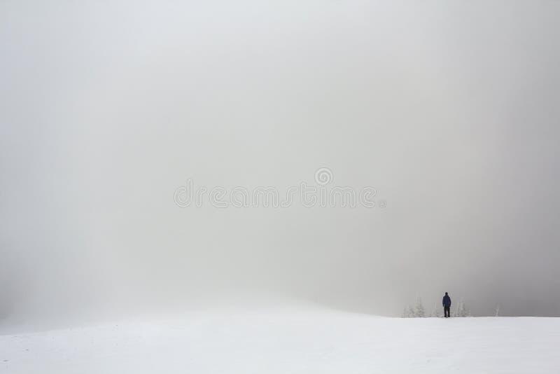 Figura lejos sola de un hombre que se coloca al aire libre en invierno imágenes de archivo libres de regalías